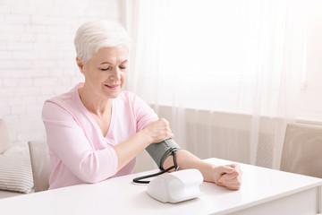 Senior lady with hypertension measuring blood pressure herself