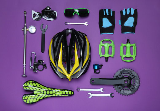Set of different bicycle tools, accessories and parts on purple background, flat lay