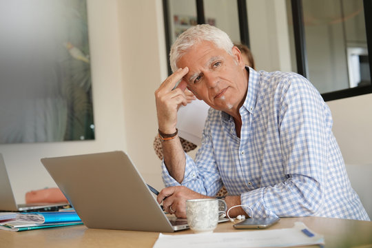 senior man working on his computer at home