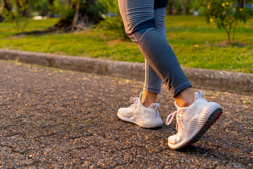Young woman walking exercise on a brown street with white shoes exercising Fotomurales
