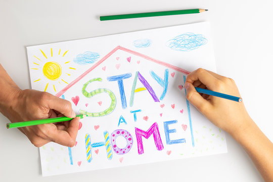 Quarantine at home during coronavirus pandemic. Kid and mother hands drawing with coloring pencils picture with words Stay at home. Social media campaign for coronavirus prevention