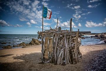 Cabane d'un Robinson Crusoé munie d'un drapeau français sur une plage. Illustration sur le confinement,l'isolement, leslogements précaires, sdf,  sans-abris de France Wall mural