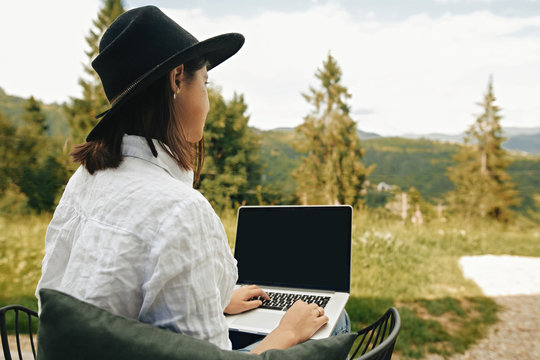 Freelance. Hipster girl with laptop sitting on wooden porch with beautiful view on woods and mountains. Stylish Young woman in hat using laptop, shopping or working online outside.