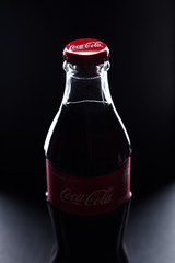 glass bottle of coca cola on black background close-up