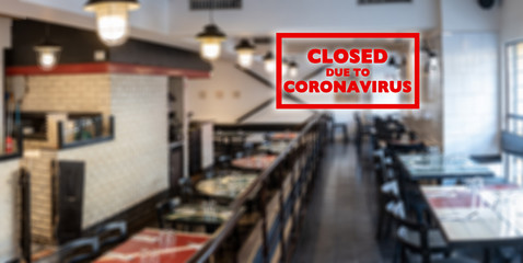 Closed due to coronavirus sign on defocused empty restaurant room