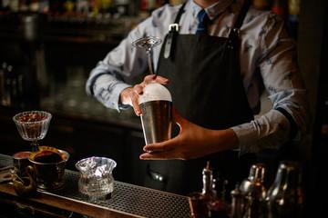 Spoed Foto op Canvas bartender in black apron preparing to make cocktail.