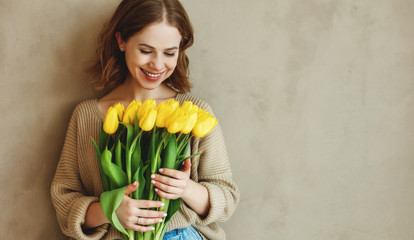 happy laughing woman with a bouquet of yellow tulips . Fotoväggar