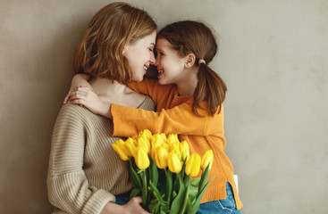 child daughter   gives mother   bouquet of flowers  yellow tulips.