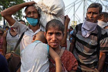 A migrant worker holding her baby cries after she missed out on receiving free food outside Howrah railway station after India ordered a 21-day nationwide lockdown to limit the spreading of coronavirus disease (COVID-19), in Kolkata