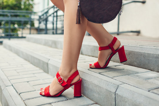 Stylish shoes and accessories. Young woman wearing fashionable red high-heeled sandals and holding handbag