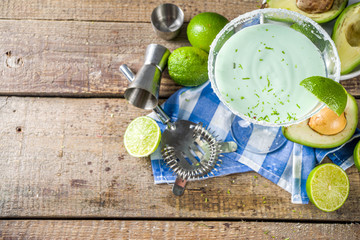 Alcoholic cocktail recipes and ideas. Avocado and lime margarita with salt, rustic wooden table copy table