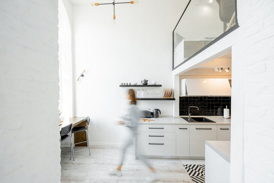 Interior view of the bright and modern kitchen with a blurred in motion human figure