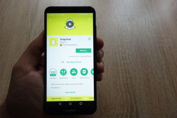 KONSKIE, POLAND - JUNE 17, 2018: Snapchat app on Google Play Store website displayed on Huawei smartphone in man`s hand