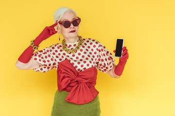 Fashionable senior woman pointing with finger on head and holding smartphone isolated on yellow Wall mural