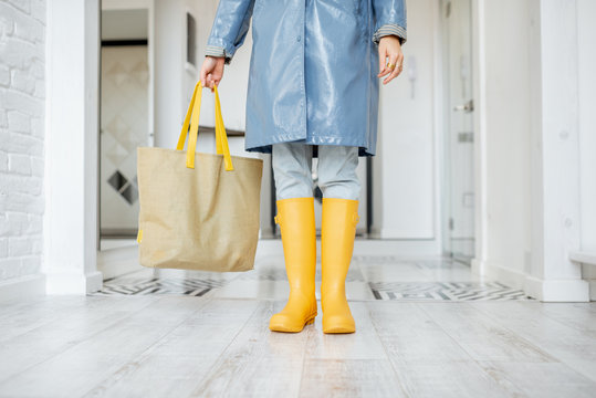 Woman in yellow rubber boots and raincoat standing with shopping bag in the corridor at home, ready to walk outside in rainy weather