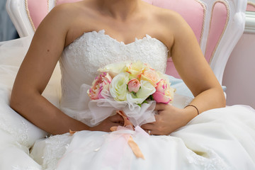 The bride holds a beautiful wedding bouquet of pink and white flowers in her hands