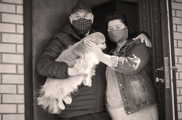 Family man and woman in mask with pet on street because of air pollution and epidemic in city. Protection against virus, infection.