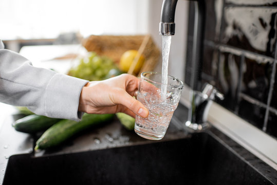 Woman filling drinking glass with tap water on the kitchen. Concept of clean drinking tap water at home