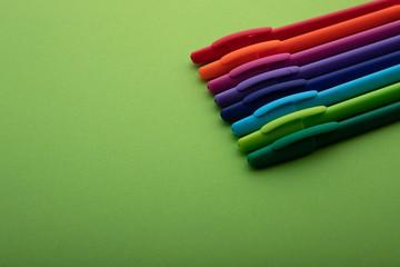 Obraz Kolorowe długopisy na zielonym tle. Przybory biurowe. - fototapety do salonu