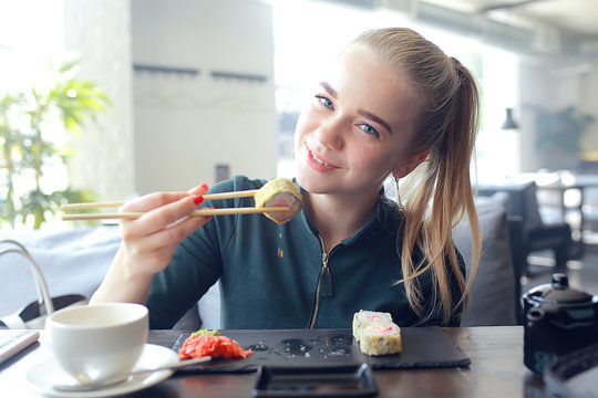 girl eats sushi and rolls in a restaurant / oriental cuisine, Japanese food, young model in a restaurant