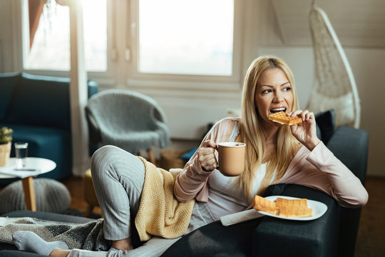 Young woman eating waffles and drinking coffee while relaxing at home.