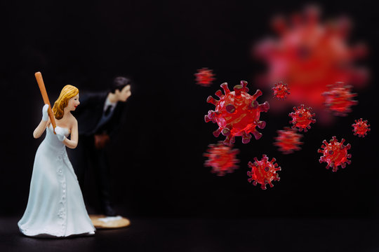 Bride and Groom holding baseball bat hitting Covid-19 Coronavirus cell coming to attack and destroy wedding ceremony.Social distancing.Lover couple Fight back virus corona covid19.Black background.