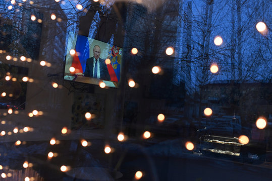 A TV set broadcasting Russian President Vladimir Putin's address to the nation on measures to combat the spread of coronavirus disease (COVID-19) is seen through the window of a cafe in Omsk