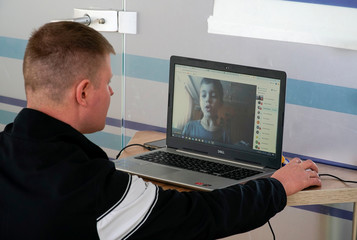 A teacher leads a lesson with students online using a computer in a private school amid coronavirus disease (COVID-19) outbreak in Minsk