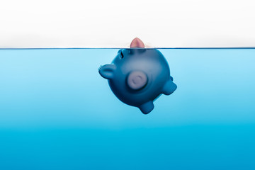 piggy bank going under blue water isolated on white, coronavirus crisis concept