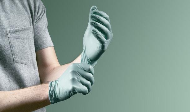 Mann zieht Einweghandschuhe an um sich vor Virus zu schützen
