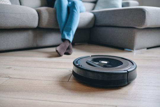 Robotic vacuum cleaner on wood floor in modern living room