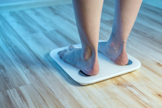 Women's bare feet stand on the floor electronic scales to check the weight and control the set of extra pounds