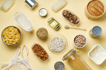 Creative flatlay with pantry staples. Glass jars with pasta, beans and chickpeas, canned goods, nuts and dried mushrooms in reusable containers. Top view pattern with basic products
