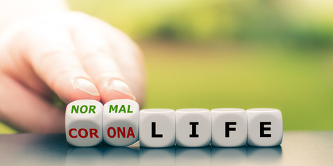 "Back to normal. Hand turns dice and changes the expression ""corona life"" to ""normal life""."