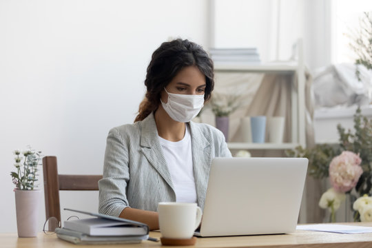 Female employee wear medical protective mask from covid-19 coronavirus pandemic work on laptop in office, woman in face cover from corona virus busy using computer at workplace, epidemic concept