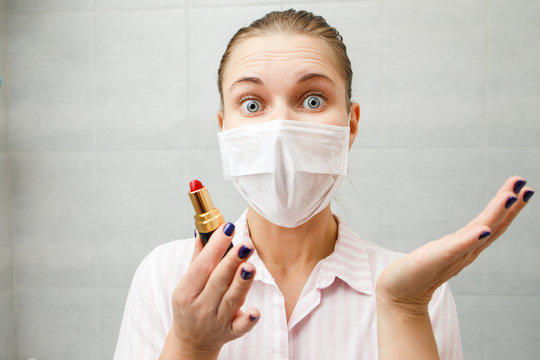 Close-up of young blonde in medical mask with lipstick in her hand