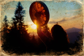 beautiful shamanic girl playing on shaman frame drum in the nature, old photo effect. Wall mural