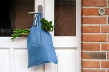 Blue shopping bag with fresh vegetables and goods was hanged on the front door, help concept during quarantine time because of coronavirus infection, copy space, selected focus