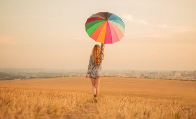Stylish woman with umbrella walking in golden field Wall mural