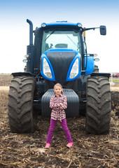 Fototapete - Cute girl near the modern tractor in the field.