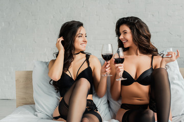 happy sexy lesbians in lingerie holding glasses of wine in bedroom