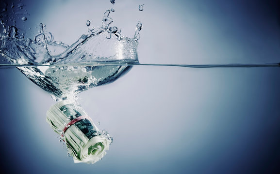 Close up US Dollar bills sinking in water as symbol of global economic and financial crisis and recession. Horizontal image.