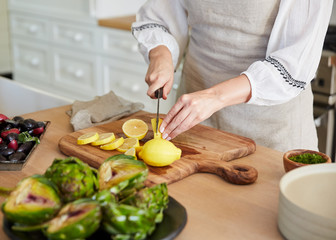 Woman in kitchen slicing lemons for cooking