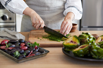 Woman in kitchen cutting herbs for cooking