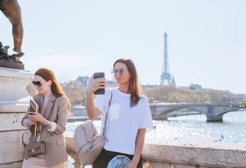 Two friends taking pictures on the Alexandre III bridge in Paris France