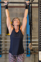 A fit woman in her seventies smiles confidently looking up at the pull up bar.