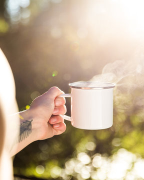 Blank white enamel coffee mug held by a hand in the forest