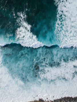 Aerial drone view of spashing waves in blue ocean