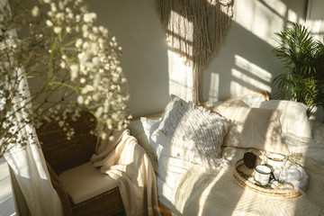 Cozy boho style sunny bedroom with light and shadows and close up of white gypsophila flowers. Authentic real life interior Fotoväggar