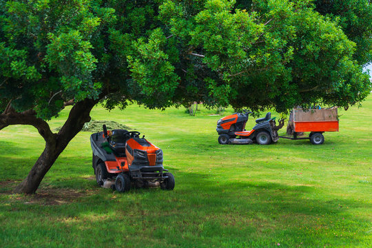 Lawn mower machines on green field. Summer garden ritual